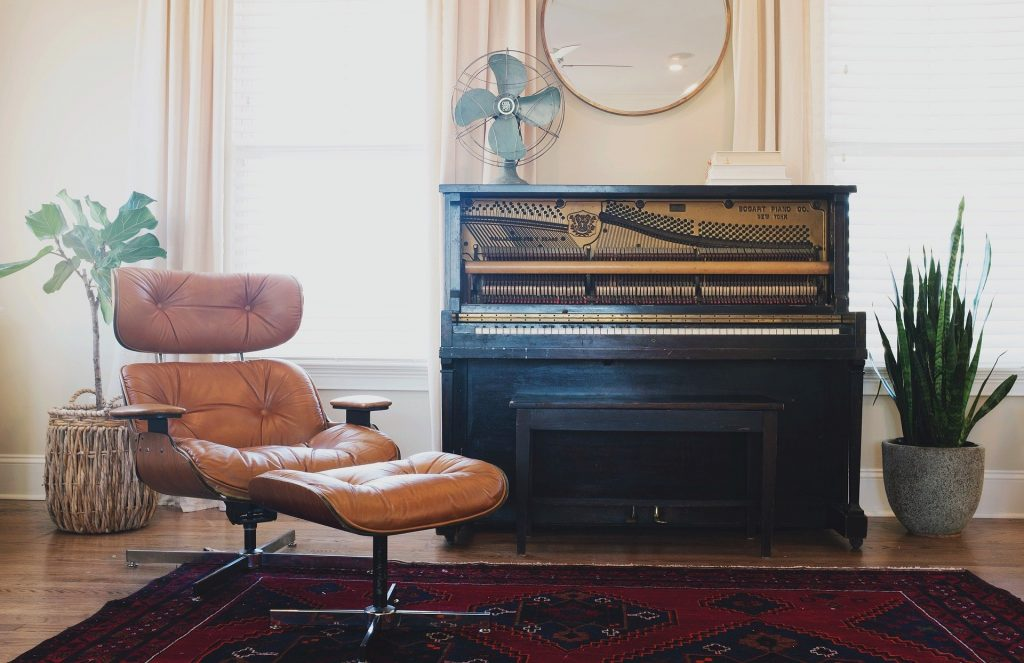 A part of a living room with two plants, a carpet, a piano, and an armchair.
