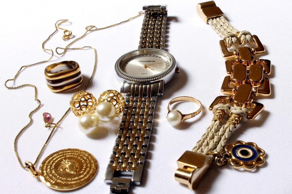 A watch surrounded by gold jewelry.