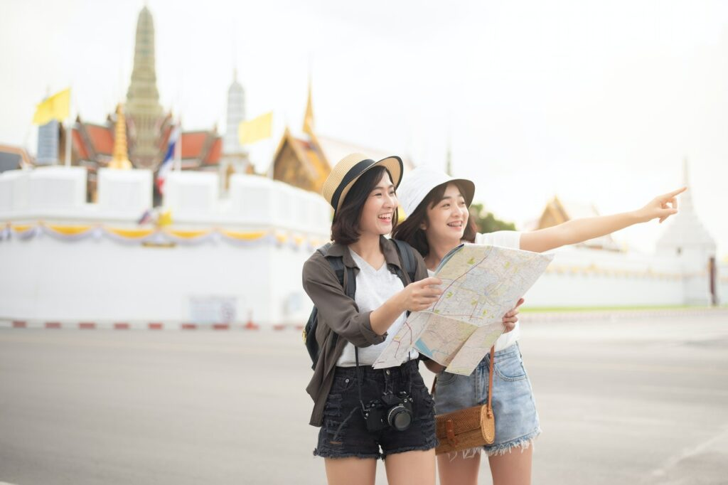 Two young women holding a map and looking happy.