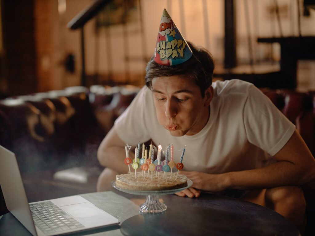 A young man with a birthday cake, blowing out the birthday candles.